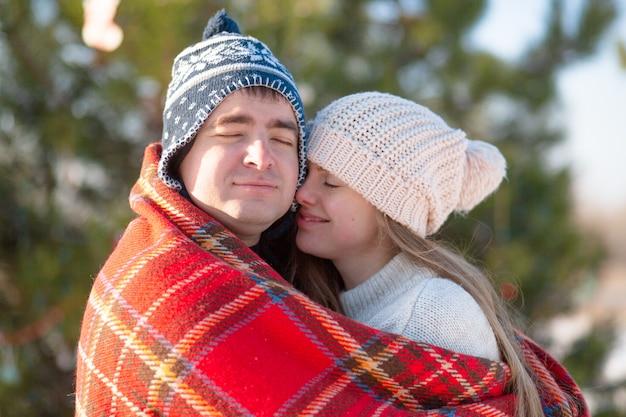 Passeggiata invernale attraverso i boschi. il ragazzo con la coperta scozzese rossa avvolge la ragazza in modo che si riscaldi