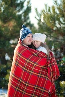 Passeggiata invernale attraverso i boschi, il ragazzo con la coperta scozzese rossa avvolge la ragazza in modo che si riscaldi