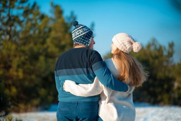 Passeggiata invernale attraverso i boschi. vista posteriore un ragazzo con una ragazza in un abbraccio a piedi nella foresta invernale