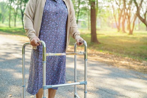Passeggiata paziente della donna anziana anziana o anziana della signora anziana con il camminatore in parco