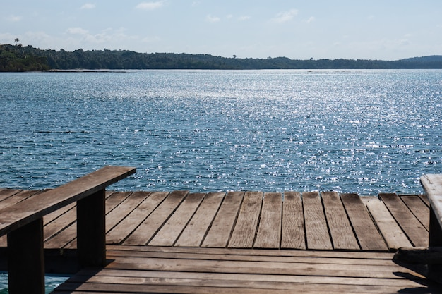 Passerella in legno con posti a sedere al mare e spiaggia in estate