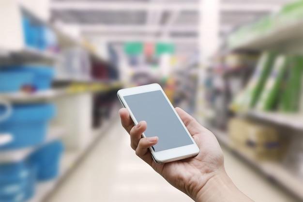 Passi a tenuta lo smart phone mobile con lo schermo di monitor in bianco sulla sfuocatura del supermercato, concetto di affari