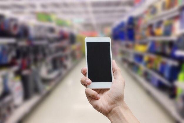 Passi a tenuta lo smart phone mobile con lo schermo di monitor in bianco sulla sfuocatura del supermercato