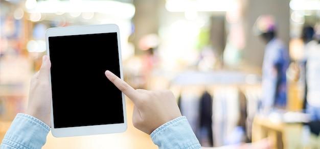 Passi facendo uso della compressa con lo schermo in bianco per derisione su sopra il fondo del negozio di sfuocatura