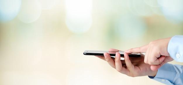 Passi facendo uso dello smartphone sopra la luce del bokeh della sfuocatura, l'affare e la tecnologia, internet del concetto di cose