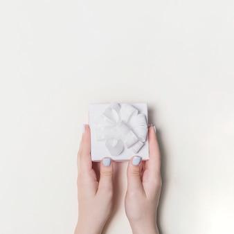 Passi il contenitore di regalo della tenuta decorato con il nastro bianco su fondo in bianco
