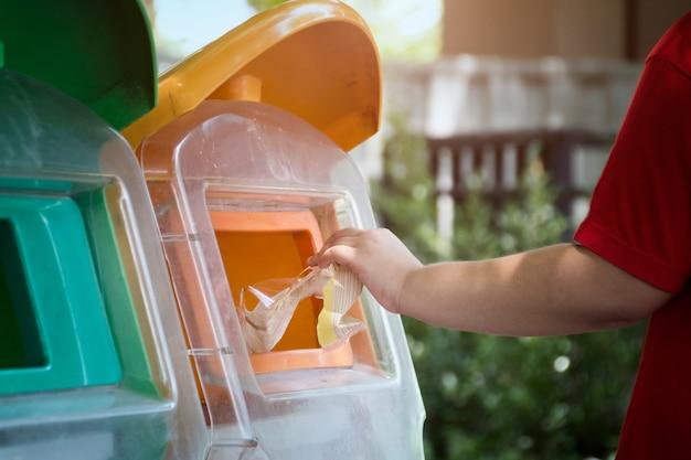 Passi il sacchetto di plastica di lancio nel recipiente di riciclaggio, concetto di protezione dell'ambiente