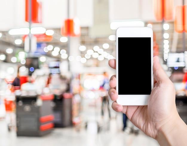 Passi il telefono cellulare della tenuta con il cliente della sfuocatura al fondo del deposito del supermercato