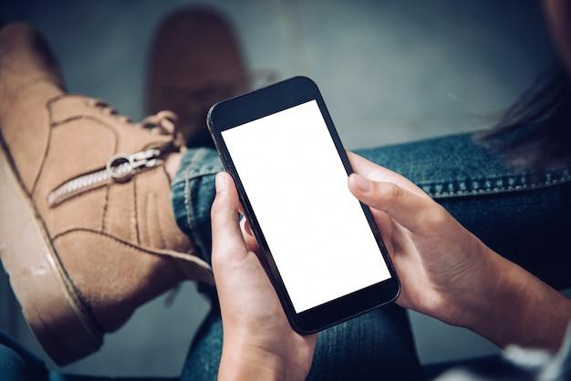 Passi il telefono cellulare della tenuta con lo schermo bianco in bianco sulla coscia con il pavimento di mattonelle delle scarpe di tela in caffè