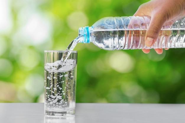 Passi l'acqua potabile di versamento nella bottiglia della forma di vetro sulla tavola con il fondo verde della sfuocatura