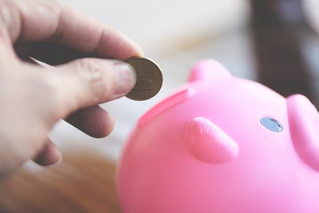 Passi l'uomo che mette la moneta dei soldi nel porcellino salvadanaio alla fine della tavola a casa su. risparmiare denaro per il concetto di borse di studio