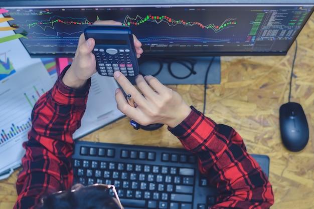 Passi l'uomo che preme sul calcolatore con il calcolo circa la dimensione o il profitto del lotto con il commercio di investimento del grafico del candlestick del mercato azionario