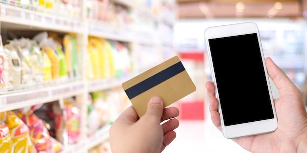 Passi la carta di credito e lo smart phone della tenuta con lo schermo in bianco sopra il supermercato della sfuocatura, immagazzini le sedere
