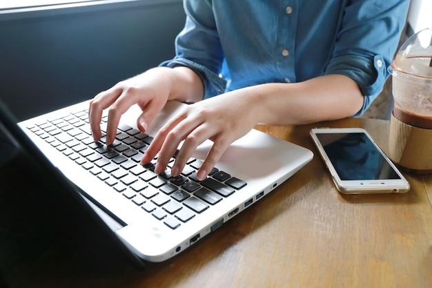 Passi la donna a funzioni multiple che lavora al computer portatile e al telefono che collegano internet wifi.