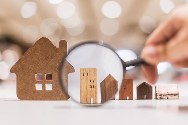 Passi la lente d'ingrandimento della tenuta e l'esame del modello della casa