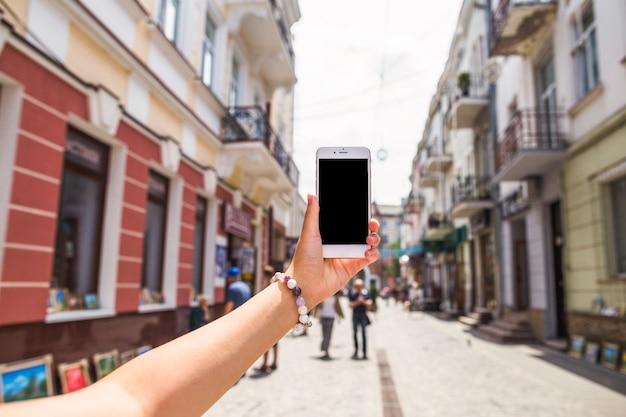 Passi la maschera di presa della via occupata della città tramite il telefono cellulare