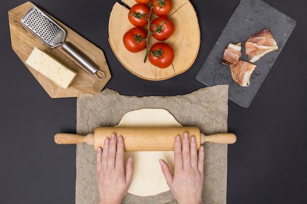 Passi la pasta della pizza di rotolamento sulla carta pergamena con l'ingrediente della pizza su fondo nero