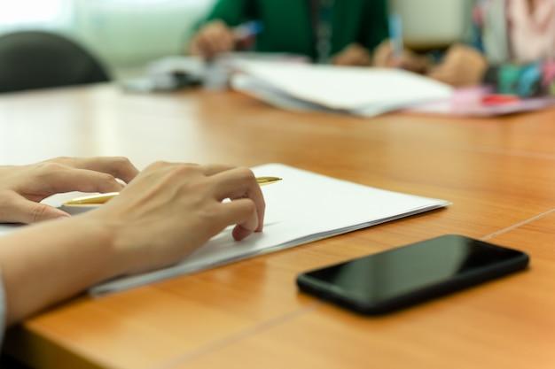 Passi la penna di tenuta mentre presentano il suo documento nella riunione dell'ufficio.