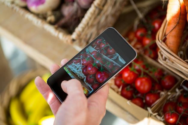 Passi la presa della foto dei pomodori ciliegia nell'esposizione nella sezione organica