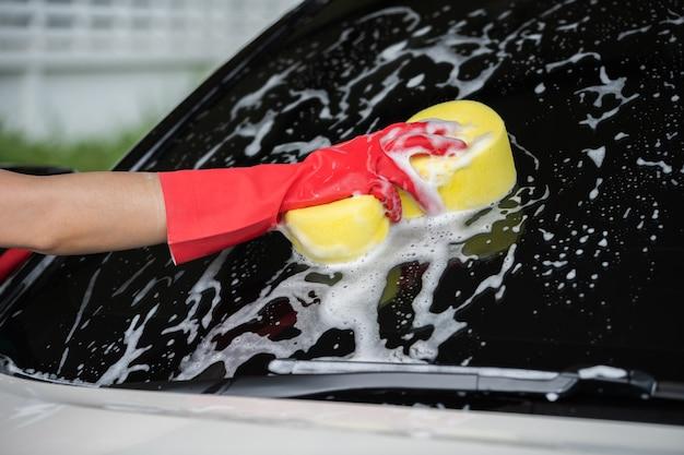 Passi la spugna della tenuta a lavare la finestra dell'automobile
