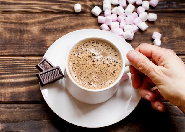 Passi la tenuta del cappuccio di caffè sul piccolo piatto con due piccoli cioccolato e caramelle gommosa e molle sul tavolo