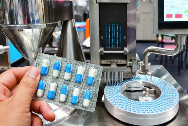 Passi la tenuta del pacchetto blu della capsula alla linea di produzione della pillola della medicina, concetto farmaceutico industriale.