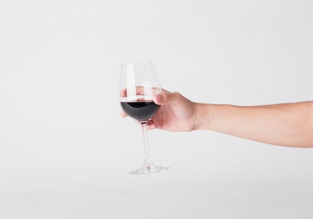 Passi la tenuta del vetro del vino rosso su un fondo bianco.