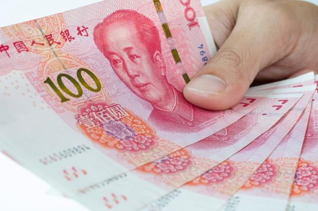Passi la tenuta della banconota degli yuan della cina su bianco. la banconota yuan è la valuta di cambio principale e popolare nel mondo