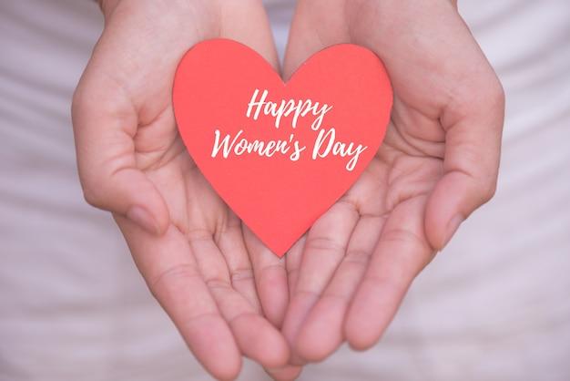Passi la tenuta della carta del cuore rosso con il concetto del messaggio del giorno delle donne felici.