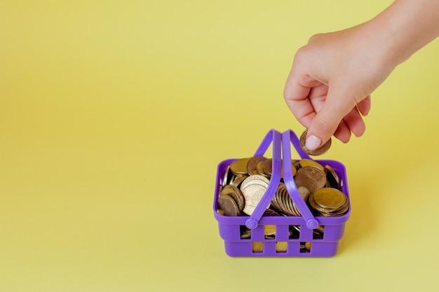 Passi la tenuta della moneta con il mucchio della moneta nel cestino della spesa su giallo