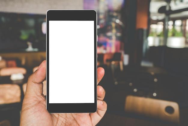 Passi la tenuta dello smart phone mobile nero con lo schermo nero in bianco nel caffè della caffetteria.