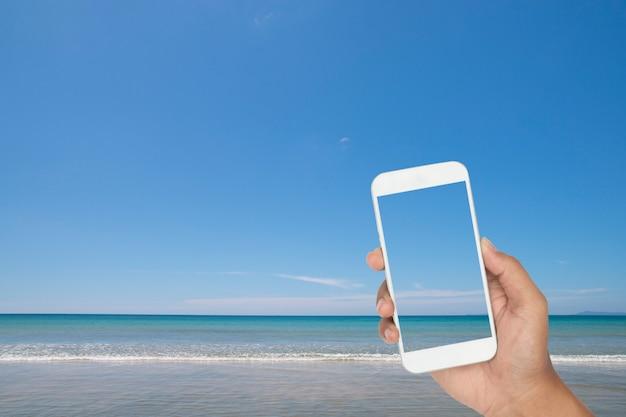 Passi la tenuta dello smartphone con il mare tropicale e la spiaggia come fondo