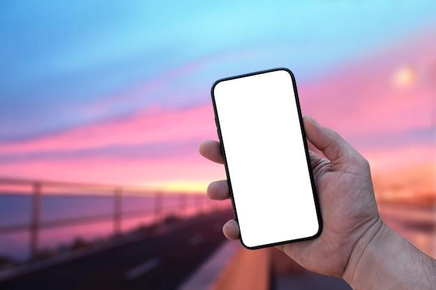 Passi la tenuta dello smartphone in bianco contro la tavola dell'alba del mare.