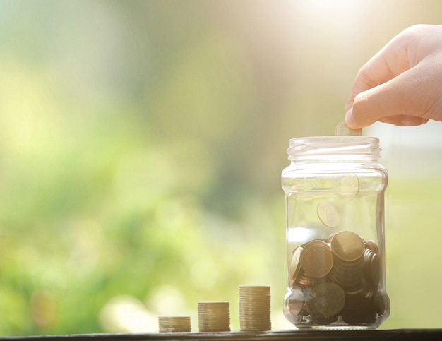 Passi le monete dei soldi di goccia per riempire. risparmio di denaro concetto.