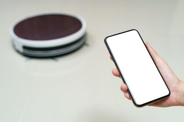 Passi lo smartphone della tenuta con lo schermo di soppressione per l'aspirapolvere robot di controllo. concetti di tecnologia della vita intelligente.