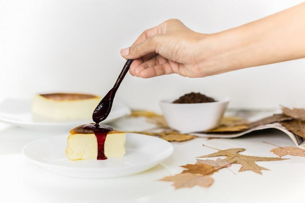 Passi mettere la salsa di bacche con il cucchiaio di legno sulla cheesecake.