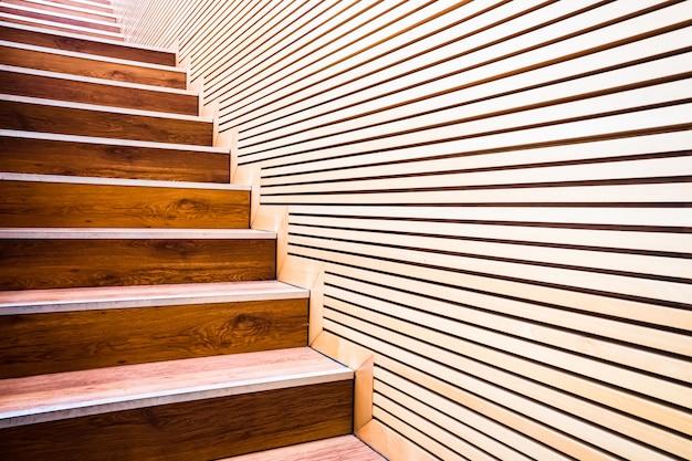 Passi su una scala accanto a un muro di assi di legno in edilizia sostenibile.