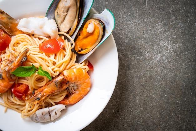 Pasta ai frutti di mare con vongole, gamberi, calamari, cozze e pomodori