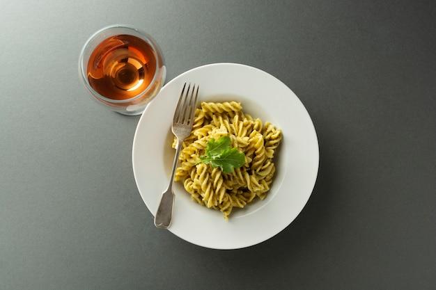 Pasta al pesto e bicchiere di vino rosato in lamiera bianca su sfondo grigio. cibo italiano.