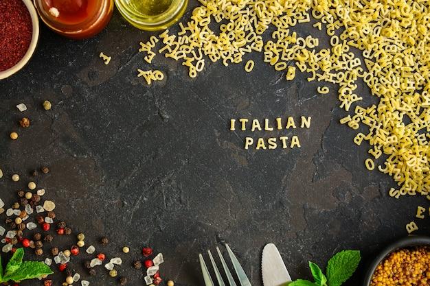 Pasta alfabeto e ingrediente per salsa (set di ingredienti, pasta cruda) che serve il secondo piatto. sfondo di cibo superiore. copia spazio