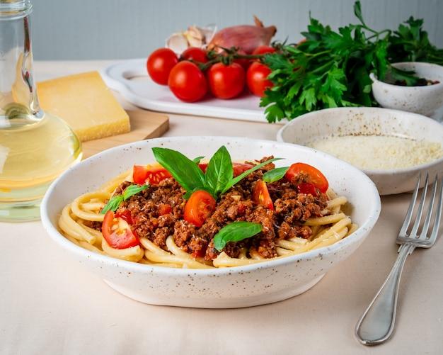 Pasta alla bolognese con salsa di pomodoro, carne macinata macinata, foglia di basilico