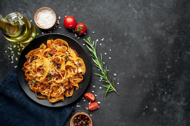 Pasta alla bolognese con spezie, piatto di pasta italiana con carne macinata e pomodori in un piatto scuro su uno sfondo di pietra