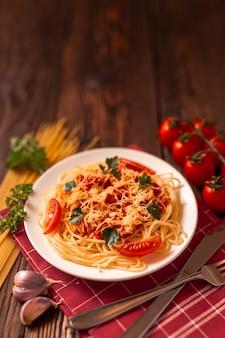 Pasta alla carbonara con salsa di pomodoro e carne macinata, parmigiano grattugiato e prezzemolo fresco