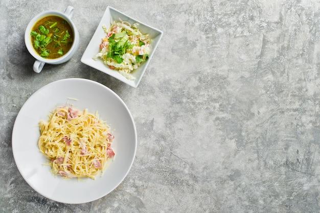 Pasta alla carbonara, insalata verde e zuppa di pollo.