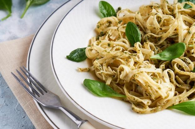 Pasta appetitosa con pesto di salsa e spinaci nel piatto sul tavolo di pietra azzurro.