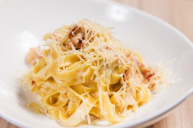Pasta con carne e formaggio in zolla bianca sulla tavola di legno leggero in un ristorante