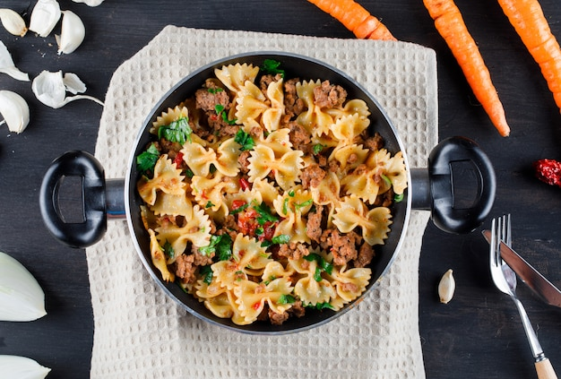 Pasta con carne in padella con cipolla, aglio, carote, forchetta, coltello