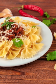 Pasta con carne, salsa di pomodoro e verdure sul tavolo