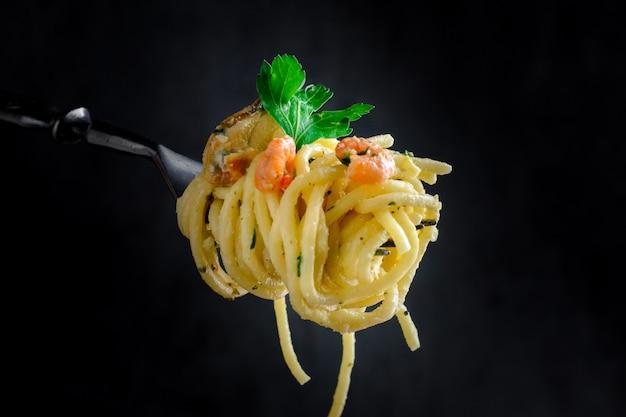 Pasta con cozze e gamberi su una forcella su uno sfondo scuro