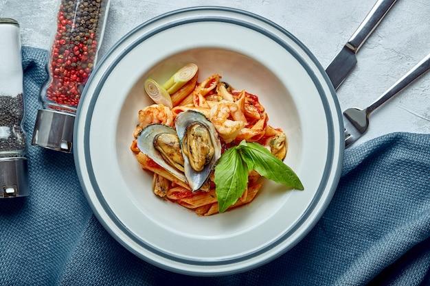 Pasta con frutti di mare e salsa di pomodoro. penne con gamberi, polpi, cozze, vongli al pomodoro e basilico